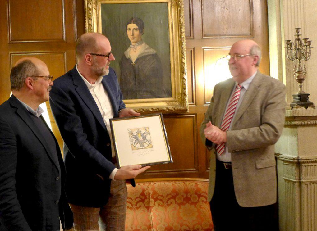 Benedikt Stampa erhält als Dank für sein Kommen einen Presseraben. Durch den Abend führten Roland Seiter (links) und Detlev Gawron.